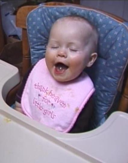 Sabrina laughing in her high chair