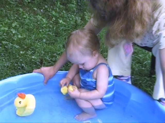 Sabrina playing with rubber duckies in her wading pool